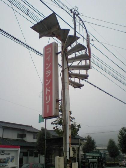 超芸術トマソンの一例  看板の柱に無意味な螺旋階段が・・・